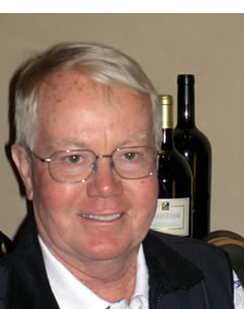 John Mckay headshot with wine bottles